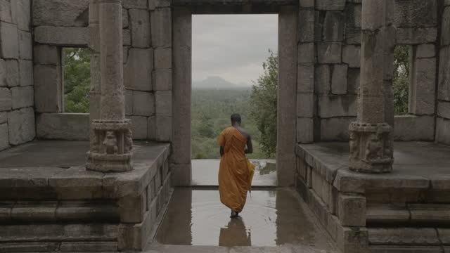 monk walks through archway at yapahuwa, sri lanka. - sri lankan culture stock videos & royalty-free footage