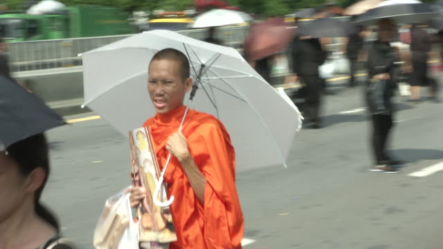 a monk walks towards sanam luang where the funeral and cremation of the late king of thailand bhumibol adulyadej - king of thailand stock videos and b-roll footage