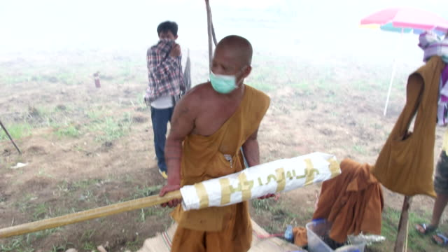 a monk works on a giant homemade rocket t be launched as a gesture to god for the sake of the rainy season during the ban bung fai rocket festival in... - monk stock videos and b-roll footage