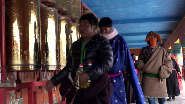 monks and believers walking around prayer wheel in lama temple,sichuan,china. - garze tibetan autonomous prefecture stock videos & royalty-free footage