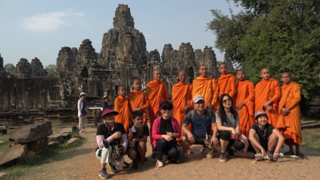 Monks and tourists being photographed at giant stone face tower of Bayon temple