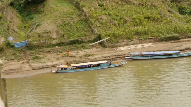 monks getting off a boat in nong khiaw. laos - spoonfilm stock-videos und b-roll-filmmaterial