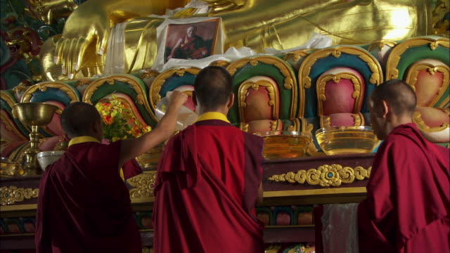 monks make offerings of incense at an altar. available in hd. - altar stock videos & royalty-free footage