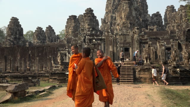 zo / monks photograph themselves at giant stone face tower of bayon temple - cambodia stock videos and b-roll footage