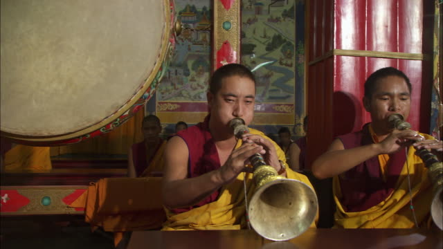Monks play horns and beat on a drum in Buddhist rituals at the Sakya Center monastery in Dehradun, India. Available in HD.