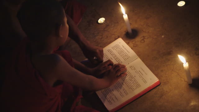 monks reading book under candle light in the dark temple - buddha stock videos & royalty-free footage