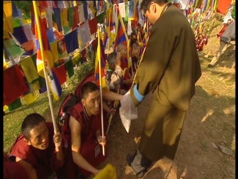 monks squatting on the ground reach into a bag for a handful of chalk - handful stock videos & royalty-free footage