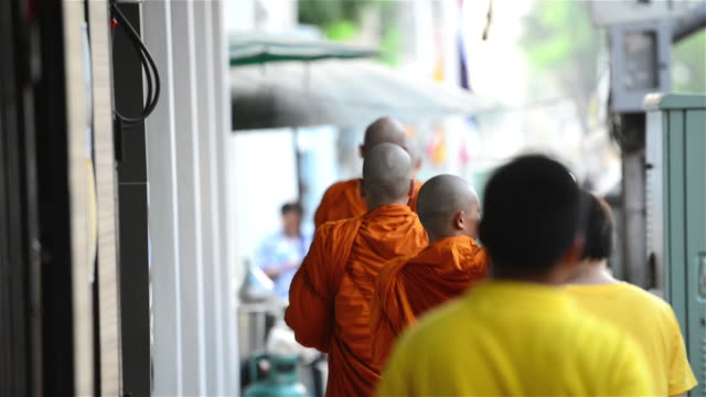 monks walking in line during morning hours of bangkok - alm stock-videos und b-roll-filmmaterial