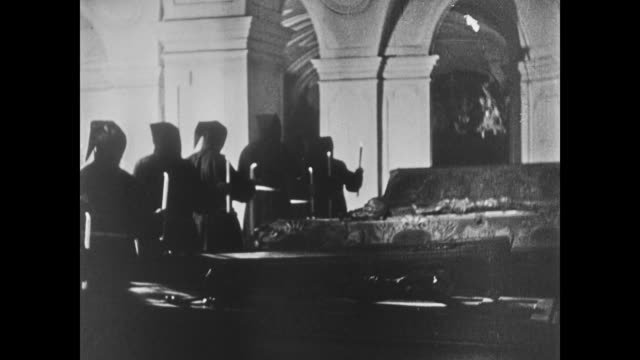 monks walking past imperial sarcophagi in crypt of habsburg family. monks kneeling at sarcophagus. man in silhouette looking into crypt through gate. - impero video stock e b–roll