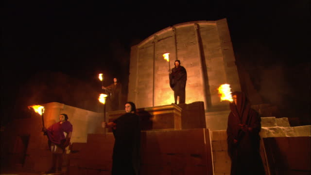 monks wave flaming torches as they stand outside a temple. - historical reenactment stock videos and b-roll footage