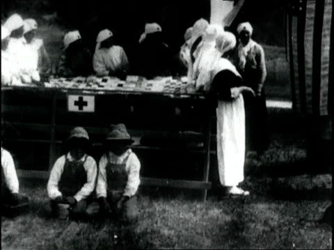 mono indian women in red cross uniforms knitting a large quilt blanket / mono indian woman teaching elderly mono indian man how to sew. mono indians... - 1918 stock videos & royalty-free footage
