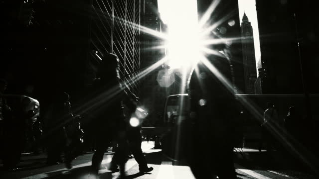 Mono silhouette shot of people walking under bright sunlight at rush hour in the New York City