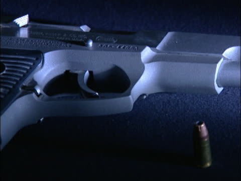 monochromatic close up of a bullet and a handgun. - handgun stock videos and b-roll footage