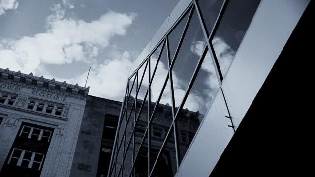 vídeos y material grabado en eventos de stock de monochrome architectural detail with modern glass windows contrasted with early 20th century stone building. - imagen virada