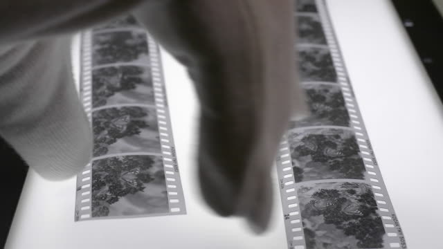 monochrome film negatives and lupe magnifier on a light box. - negatives stock videos & royalty-free footage
