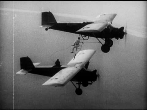 monoplane in flight, crowd on street looking up, some w/umbrellas, aerial forest o'brine & dale jackson in curtiss 'robin' airplane w/ another above,... - 1920 1929 stock videos & royalty-free footage