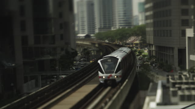 monorail between inner city buildings. - monorail stock videos and b-roll footage
