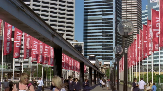 Monorail passing over pedestrians crossing Pyrmont Bridge lined with banners / Darling Harbour, Sydney, Australia