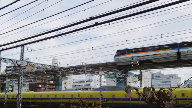 vidéos et rushes de ms monorail to passing overhead and below bullet train / tokyo, tokyo-to, japan  - monorail