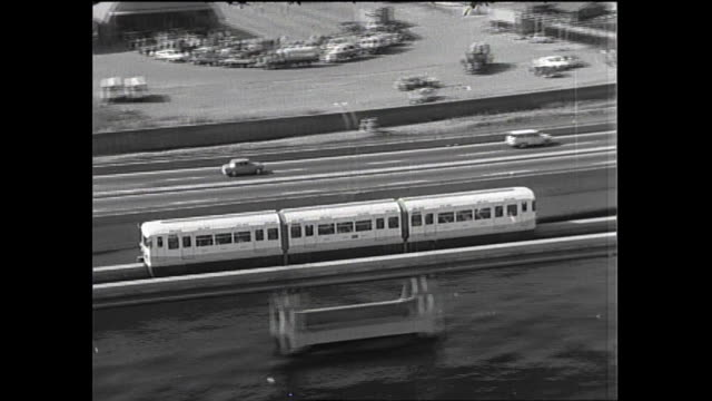 vidéos et rushes de monorail train runs parallel to vehicle on the tokyo metropolitan expressway / shot at shinagawa area in tokyo on october 5 1965 - monorail