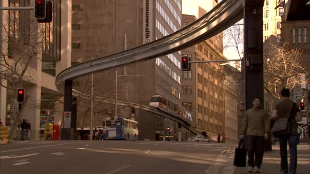 la ws tu monorail traveling on track above city street near centrepoint tower / sydney, australia - pendlerzug stock-videos und b-roll-filmmaterial