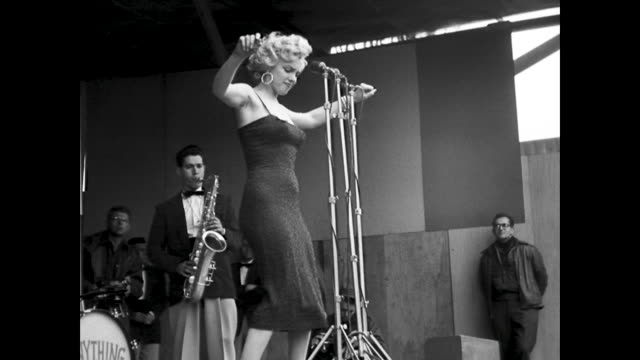 stockvideo's en b-roll-footage met monroe dances and sings for the gis sings with a quartet of men accompanying her - marilyn monroe