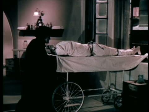 monster in hat + cloak dumps sheeted body out of window - död koncept bildbanksvideor och videomaterial från bakom kulisserna