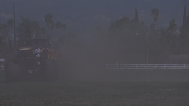 A monster truck kicking up dust and crushing cars at a county fair.