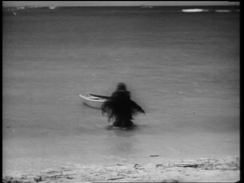 B/W 1961 monster walking out of ocean onto beach toward camera