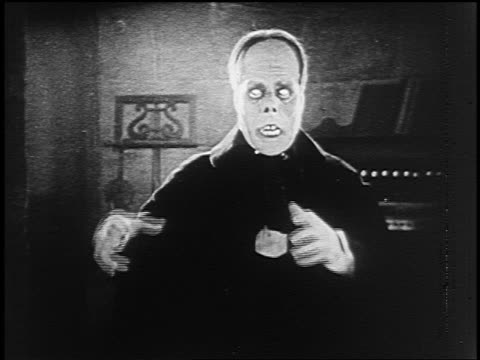 vídeos de stock, filmes e b-roll de b/w 1925 monstrous man (lon chaney, sr.) raising arms + menacing someone offscreen - assustador