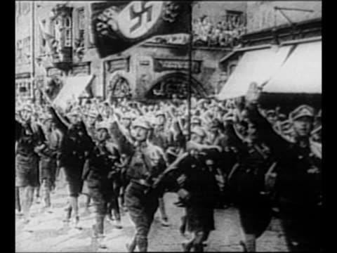 vídeos de stock, filmes e b-roll de montage adolf hitler rides through crowd, wearing brown shirt, as crowd members issue nazi salute / german soldiers walk in street with arms raised... - adolf hitler