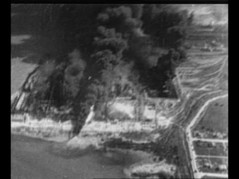 Montage aerials black smoke in harbor area / parts of destroyed vehicles in foreground skeleton of structure and smoke in background / montage...