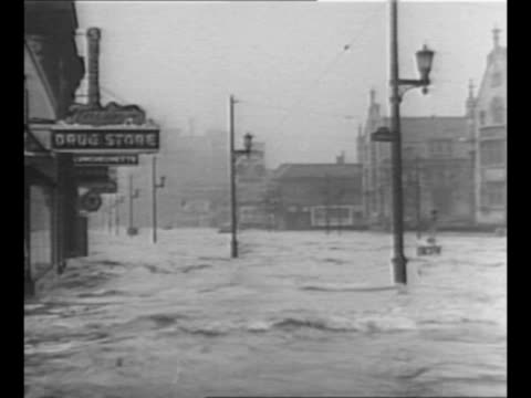 montage aerials flood in ohio river valley / very high waters in downtown area of city / men row boat across downtown area as police officer stands... - 1937 stock-videos und b-roll-filmmaterial