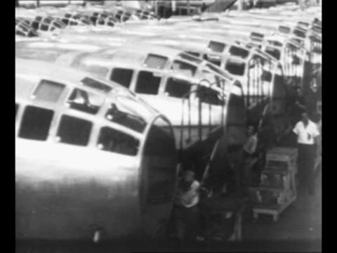 Montage aircraft factory workers at Boeing plant assemble B29 aircraft in Wichita KS during World War II fuselage nose frames engines propellers...