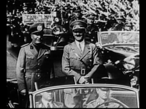 montage allies adolf hitler of germany and benito mussolini of italy ride in open car through munich with crowds issuing nazi salute as they line... - adolf hitler stock-videos und b-roll-filmmaterial