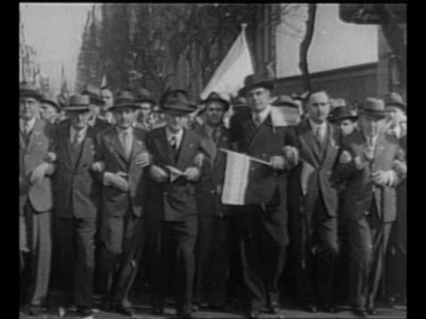 vídeos de stock e filmes b-roll de montage argentinians march in street with front row of marchers walking arm in arm / women carry large argentine flag partly filled with scraps of... - 1955