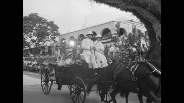montage bermudans line streets as convertible bearing queen elizabeth ii and philip, the duke of edinburgh, moves through bermuda street / archway... - bandiera del regno unito video stock e b–roll