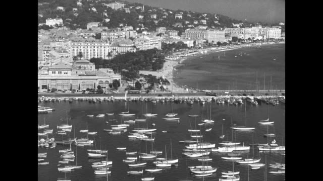 montage boats in cannes harbor / hotel du cap-eden-roc clubhouse with people nearby; tilt down to pool inlaid in rocky shoreline with bathers in it /... - cote d'azur stock videos & royalty-free footage
