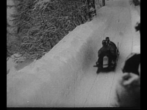 montage bobsleds move down snowy course around curves / audience watches / montage skiiers ski down hill jump land / from greatest headlines of the... - bobsleighing stock videos & royalty-free footage