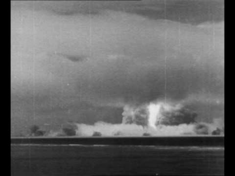 montage bomb explodes mushroom cloud rises from operation crossroads drop at bikini island / from greatest headlines of the century series - atomic bomb testing stock videos & royalty-free footage