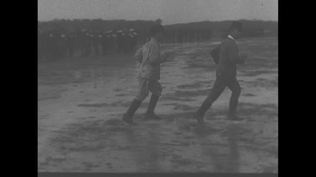 montage british soldiers search japanese pows during their formal surrender to the british in world war ii / japanese soldier walks to table in muddy... - japanese surrender stock videos and b-roll footage