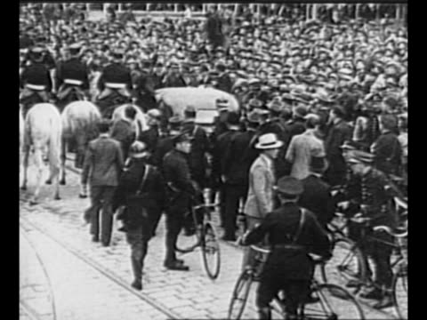 Montage car bearing assassinated Alexander I of Yugoslavia and wounded French foreign minister Louis Barthou moves through crowds / black / end...