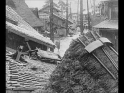 montage collapsed buildings in japanese city after earthquake/ citizens stand amidst wreckage atop collapsed houses / pan rubble and devastation on... - 1923 stock videos & royalty-free footage
