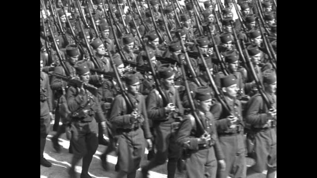 montage colonial troops march in bastille day parade in paris / black man stands in crowd, looks on solemnly / mustachioed frenchman in crowd - military parade stock videos & royalty-free footage