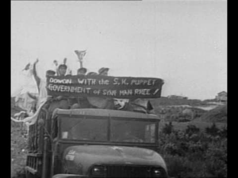 Montage Communist POWs ride in trucks after end of Korean War with sign protesting South Korean government / WS Communist POWs throw their loaned...