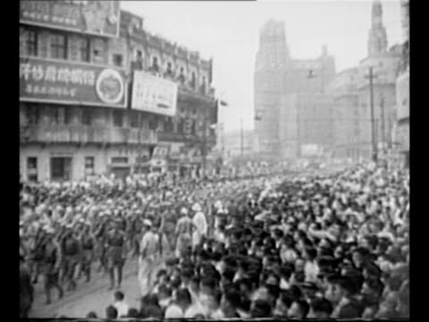 montage communist victory parade in shanghai after city is taken by communists; people march in streets with red flags and posters of mao tse-tung... - mao tse tung video stock e b–roll