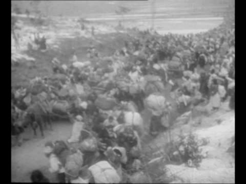 montage crowded road as korean refugees flee battle zone area during korean war carts laden with possessions line side of road as pedestrians carry... - korean war stock videos & royalty-free footage