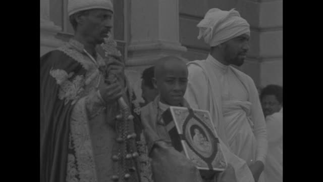 montage crowds in front of st. george's cathedral in addis ababa, ethiopia / priest leaves cathedral with aide carrying parasol, leading worshipers... - sonnenschirm stock-videos und b-roll-filmmaterial