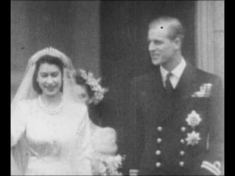 stockvideo's en b-roll-footage met montage crowds stand at the victoria memorial in london and run near buckingham palace / montage newlyweds princess elizabeth and the duke of... - prinses margaret windsor gravin van snowdon