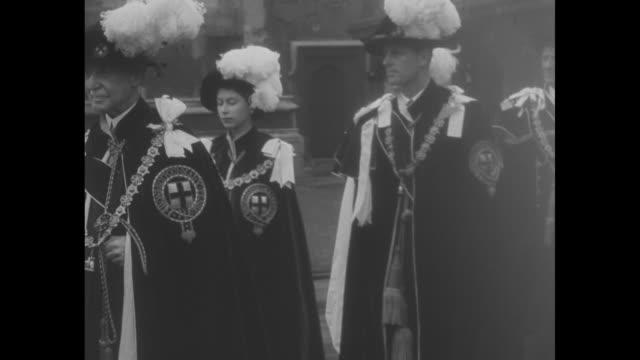 montage crowds watch procession to st. george's chapel for investiture of knights of the garter / montage princess elizabeth, duchess of edinburgh,... - hatt bildbanksvideor och videomaterial från bakom kulisserna